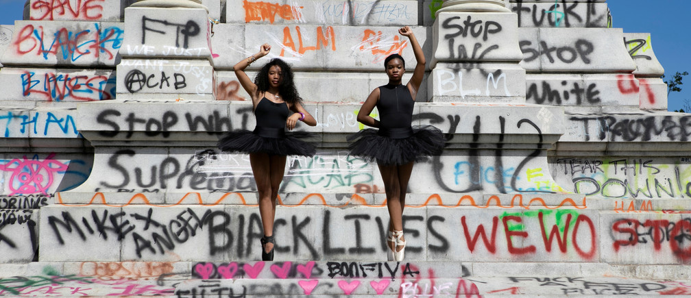 SENSITIVE MATERIAL. THIS IMAGE MAY OFFEND OR DISTURB    Ballerinas Kennedy George, 14, and Ava Holloway, 14, pose in front of a monument of Confederate general Robert E. Lee after Virginia Governor Ralph Northam ordered its removal after widespread civil unrest following the death in Minneapolis police custody of George Floyd, in Richmond, Virginia, U.S. June 5, 2020. REUTERS/Julia Rendleman     TPX IMAGES OF THE DAY - RC243H9RJZLD