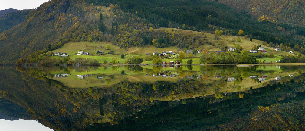 Norwegian farms are reflected in the still waters of a fjord in western Norway October 6, 2007.