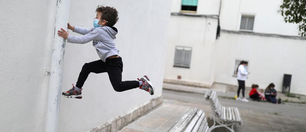 Kilian, de 6 años, lleva una máscara facial protectora mientras salta de un banco, después de que se levantaran parcialmente las restricciones para los niños, durante el brote de la enfermedad coronavirus (COVID-19), en Igualada, España, el 26 de abril de 2020.