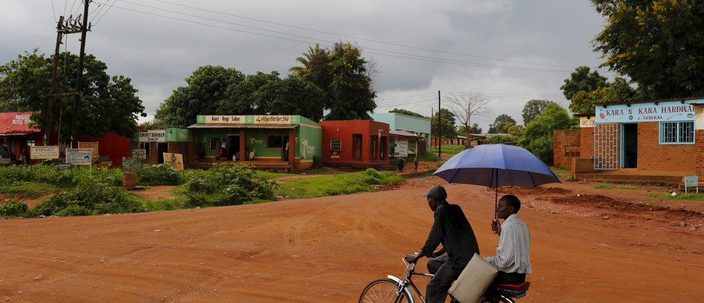 A man uses an umbrella as late rains fall near Malawi's capital Lilongwe, February 1, 2016. Late rains in Malawi threaten the staple maize crop and have pushed prices to record highs. About 14 million people face hunger in Southern Africa because of a drought that has been exacerbated by an El Nino weather pattern, according to the United Nations World Food Programme (WFP). REUTERS/Mike Hutchings - GF10000292420