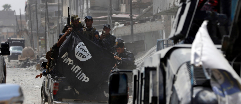 Iraqi Federal Police members hold an Islamic State flag which they pulled down during fighting between Iraqi forces and Islamic State militants in the Old City of Mosul, Iraq July 4, 2017. REUTERS/Ahmed Saad - RTX39YOT