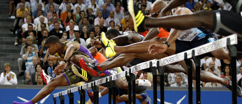 Terrence Trammell of the U.S. (in purple) clears the hurdles during the110 metres hurdles race at the  IAAF Golden League athletics meeting at the Letzigrund stadium in Zurich August 28, 2009. REUTERS/Miro Kuzmanovic (SWITZERLAND SPORT ATHLETICS IMAGES OF THE DAY) - GM1E58T07R501