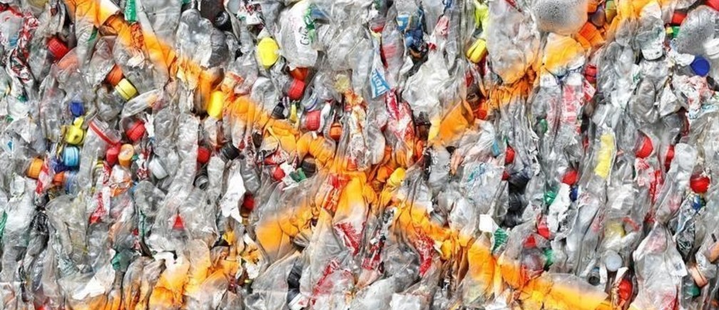 A bundle of pressed bottles made from PET (polyethylene terephthalate) plastic is stored at Poly Recycling AG company in Bilten, Switzerland April 3, 2019. REUTERS/Arnd Wiegmann - RC1167F45B90