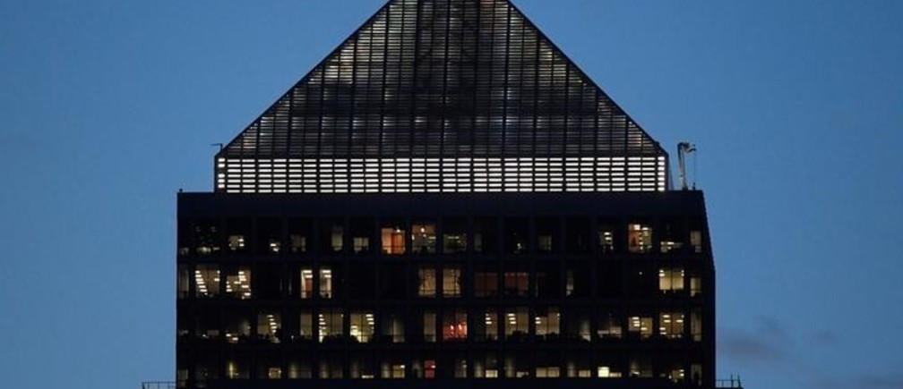 Workers are seen in an office tower in the Canary Wharf financial district at dusk in London, Britain, November 17, 2017. Picture taken November 17, 2017. REUTERS/Toby Melville