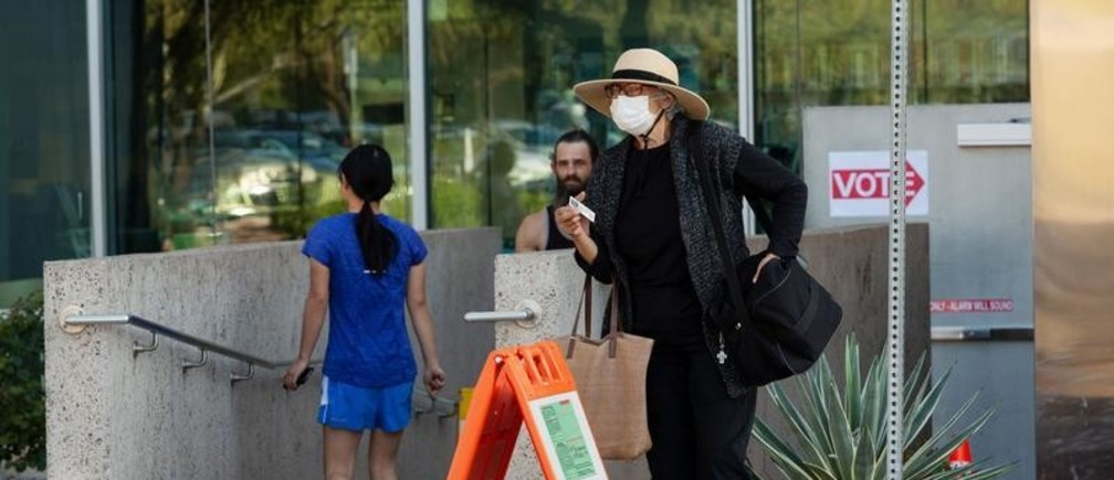 Rebeca Estrada Hasselbach, 73, leaves a polling station after casting her ballot at the Burton Barr Library, wearing a mask amid the coronavirus disease (COVID-19) concerns, in Phoenix, Arizona, U.S., March 17, 2020.  REUTERS/Cheney Orr - RC23MF9RMHBS