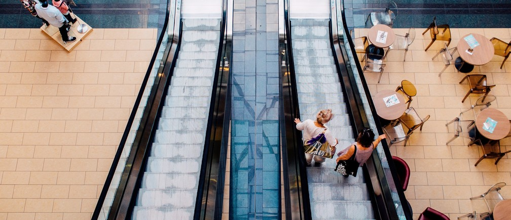 People descend an escalator to a cafe in a shopping mall