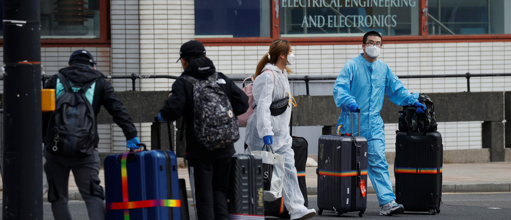 Students wearing protective face masks and clothing are seen with suitcases leaving their halls of residence at Liverpool University, as the spread of the coronavirus disease (COVID-19) continues, Liverpool, Britain, April 12, 2020.