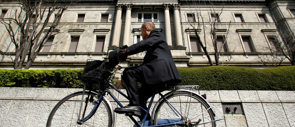 A man rides a bicycle past the Bank of Japan (BOJ) building in Tokyo, Japan March 18, 2009. REUTERS/Yuriko Nakao/File Photo  - RTX2P8PI
