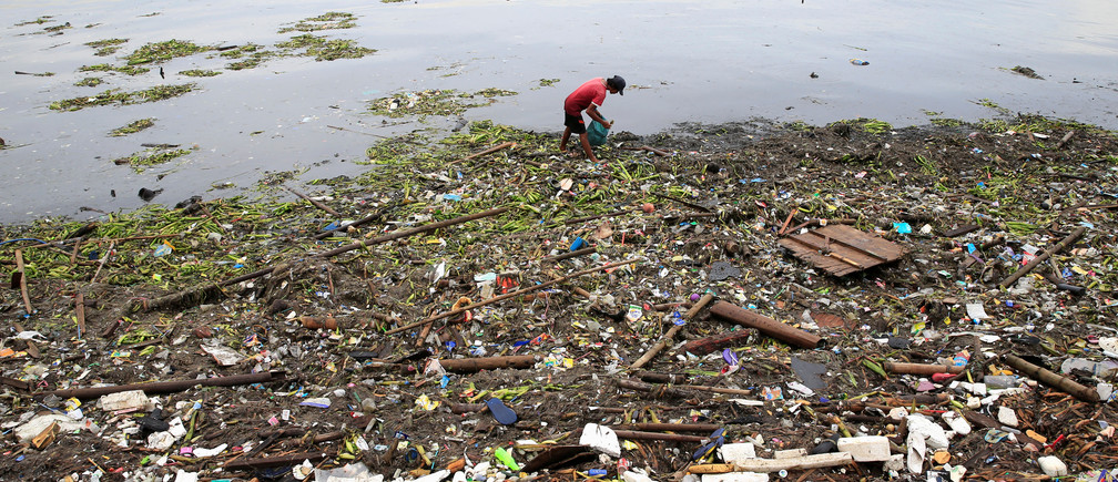 A man collects plastic bottles and other recyclable materials washed ashore along the bay brought by tropical storm Pakhar, locally named Jolina, in metro Manila, Philippines August 26, 2017. REUTERS/Romeo Ranoco - RC18384E04B0