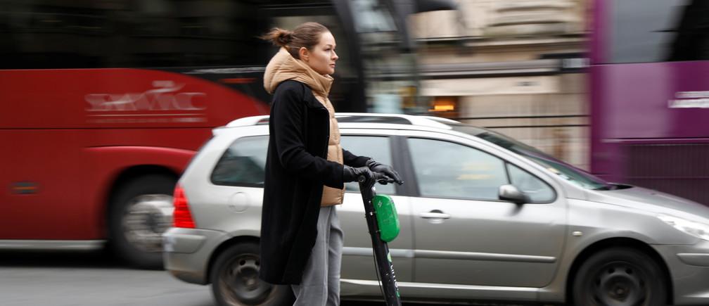 """Una mujer monta un scooter eléctrico sin muelle o una """"trotineta"""" Lime-S del servicio de bicicletas compartidas Lime, con sede en California, en una calle de París, Francia, 2019."""