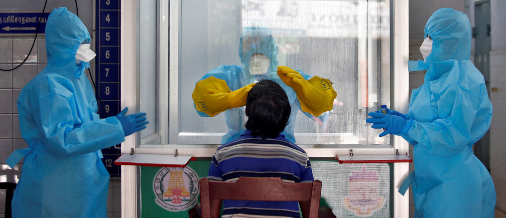 A doctor in a protective chamber takes a swab from a man to test for coronavirus disease (COVID-19) at a newly installed Walk-In Sample Kiosk (WISK) in a government-run hospital in Chennai, India, April 13, 2020. REUTERS/P. Ravikumar     TPX IMAGES OF THE DAY - RC2N3G933Q6L