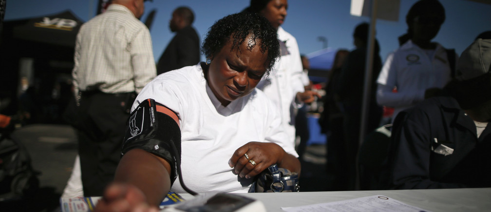 Bernita Jackson, 51, has her blood pressure measured at an event to inform people about the Affordable Care Act and donate turkeys to 5,000 needy families, in Los Angeles, California, November 25, 2013.