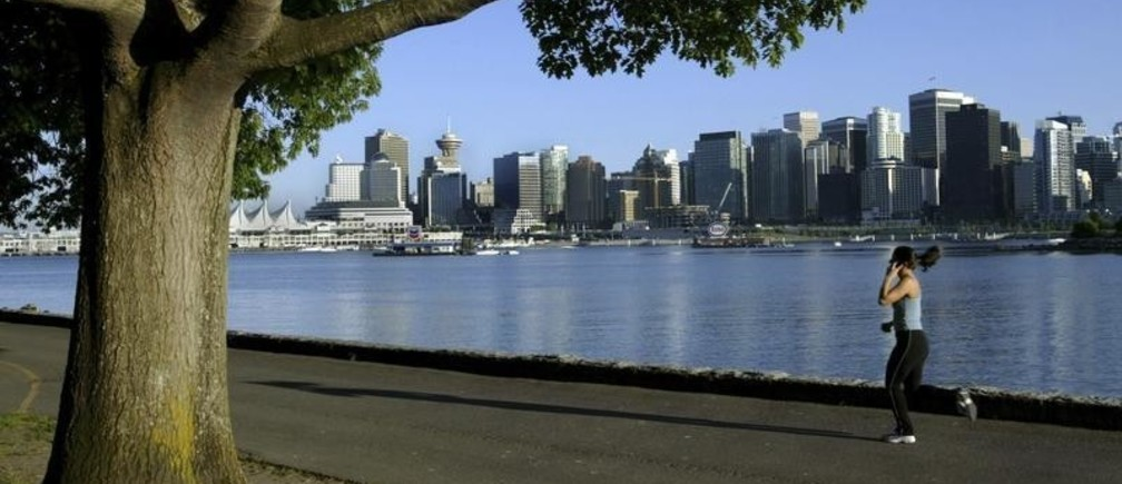A jogger runs along the seawall in Stanley Park with the city skyline in the background in this June 24, 2003 file photo. Vancouver, host of this month's Winter Olympics, prides itself on being one of the world's most liveable cities but residents seem unsure at times whether they really want the world on their doorstep.   To match feature OLYMPICS/VANCOUVER   REUTERS/Andy Clark (CANADA - Tags: SPORT OLYMPICS SOCIETY CITYSCAPE) - RTR29QQE