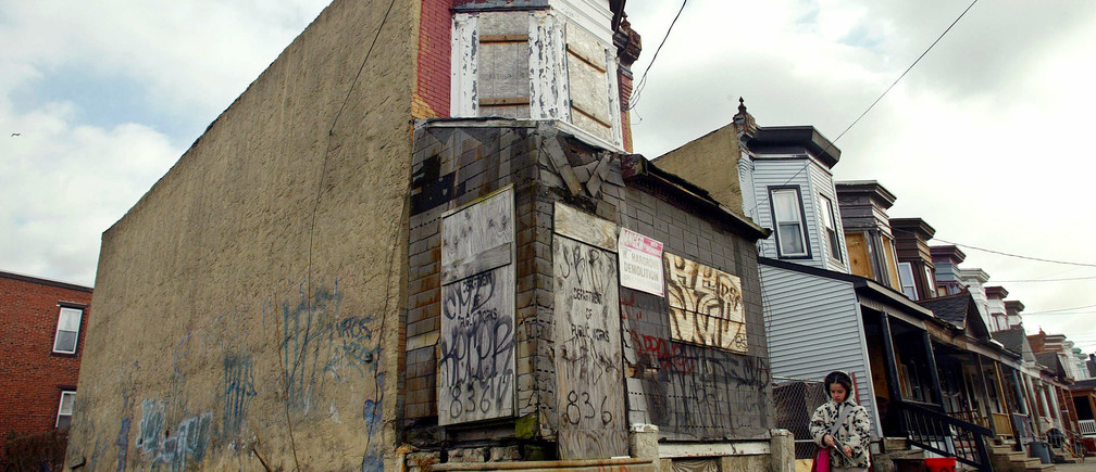 A young girl walks by an abandoned building and lot in Camden, New Jersey March 9, 2005