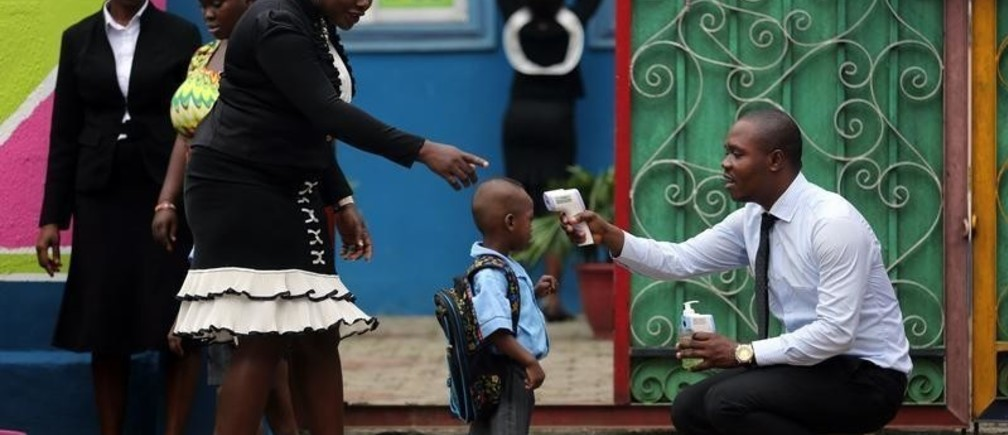 A school official takes a pupil's temperature using an infrared digital laser thermometer in front of the school premises, at the resumption of private schools, in Lagos September 22, 2014. Nigeria and Senegal, two of the five countries affected by the world's worst ever Ebola outbreak are managing to halt the spread of the disease, the World Health Organization said on Monday, although the overall death toll rose to 2,793 out of 5,762 cases. REUTERS/Akintunde Akinleye (NIGERIA - Tags: EDUCATION HEALTH DISASTER SOCIETY TPX IMAGES OF THE DAY) - GM1EA9M1U3701