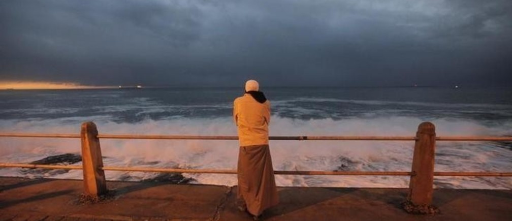 A Cape Town Muslim awaits the sighting of the crescent moon marking Eid al-Fitr, the end of Ramadan, the holiest month in the Islamic calendar, along the city's Sea Point beachfront, September 9, 2010.   REUTERS/Mike Hutchings  (SOUTH AFRICA - Tags: RELIGION SOCIETY)