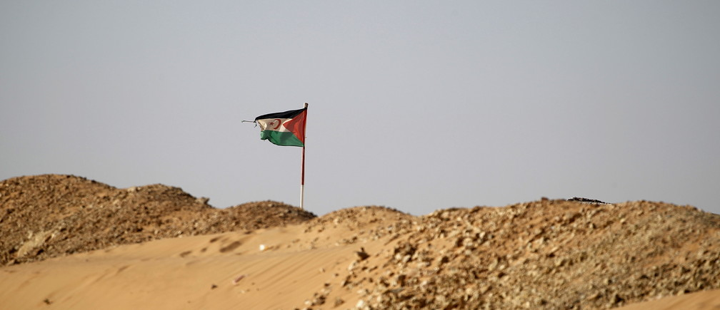 """The Sahrawi Arab Democratic Republic flag flies in Boudjdour desert refugee camp in Tindouf, southern Algeria March 4, 2016. In refugee camps near the town of Tindouf in arid southern Algeria, conditions are hard for indigenous Sahrawi residents. Residents use car batteries for electricity at night and depend on humanitarian aid to get by. The five camps near Tindouf are home to an estimated 165,000 Sahrawi refugees from the disputed region of Western Sahara, according to the United Nations refugee agency UNHCR. REUTERS/Zohra Bensemra SEARCH """"THE WIDER IMAGE"""" FOR ALL STORIES  Matching text ALGERIA-SAHARA/ - RTS9CBB"""