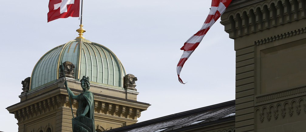 Workers hang up a Swiss flag on the Swiss parliament building in Bern, Switzerland, November 24, 2015. REUTERS/Ruben Sprich - LR1EBBO10FE8G