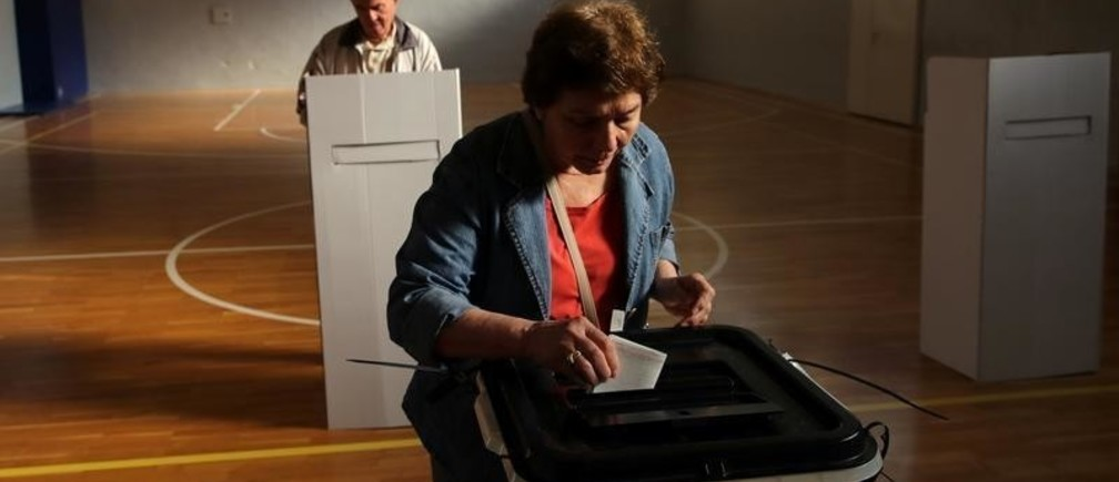 A woman casts her ballot for the referendum in Macedonia on changing the country's name that would open the way for it to join NATO and the European Union in Skopje, Macedonia September 30, 2018