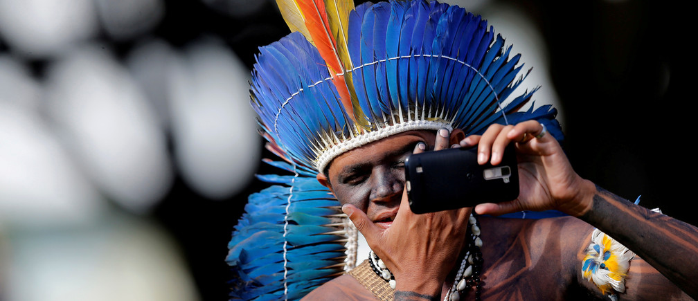 An indigenous Brazilian man checks his face in a mobile phone at the Terra Livre camp in Brasilia, April 2018.
