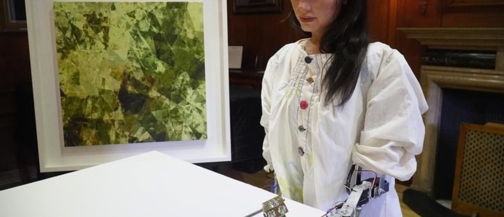 Robot artist 'Ai-Da' sketches using a pencil attached to her robotic arm, while standing next to a painting based on her computer vision data when run through algorithms developed by computer scientists in Oxford, Britain June 4, 2019. Picture taken June 4, 2019. REUTERS/Matthew Stock - RC1844958CB0