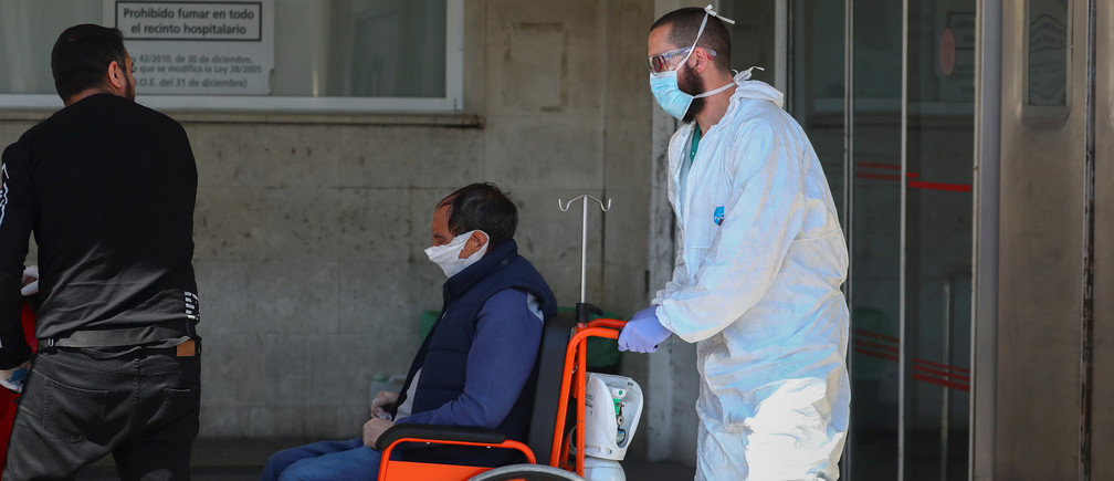 A healthcare worker wearing a protective face mask and suit pushes a patient in a wheelchair near the emergency unit at 12 de Octubre hospital during the coronavirus disease (COVID-19) outbreak in Madrid, Spain March 28, 2020. REUTERS/Sergio Perez - RC20TF9CSWTZ