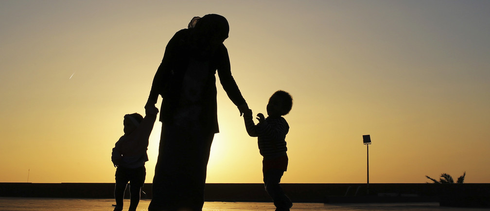 A woman walks with her two children at sunset near the seashore in Benghazi