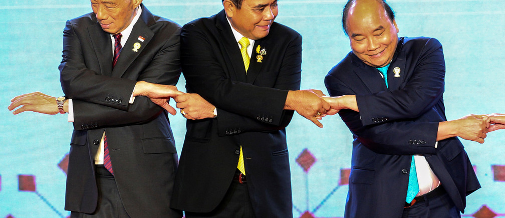 ASEAN leaders shake hands on stage during the opening ceremony of the 34th ASEAN Summit in Bangkok, Thailand, June 23, 2019. Seen here are Thai Prime Minister Prayuth Chan-ocha, chairman of the 34th ASEAN Summit, Singapore's Prime Minister Lee Hsien Loong, and Vietnam's Prime Minister Nguyen Xuan Phuc. REUTERS/Athit Perawongmetha - RC1CD09BA650