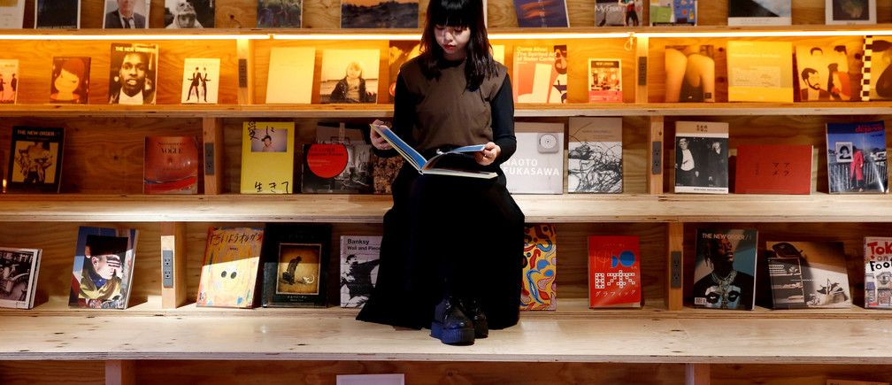 A woman reads a book at the Shinjuku branch of Book and Bed, an accommodation combined with book cafe where guests can sleep in hidden bunks built into a large bookshelf, during a photo opportunity in Tokyo, Japan September 14, 2018.