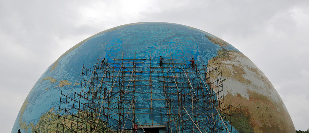 Workers remove scaffolding from a replica of planet earth after repairs at Science City in Ahmedabad, India, July 29, 2016.REUTERS/Amit Dave     TPX IMAGES OF THE DAY      - S1BETSIYPBAA