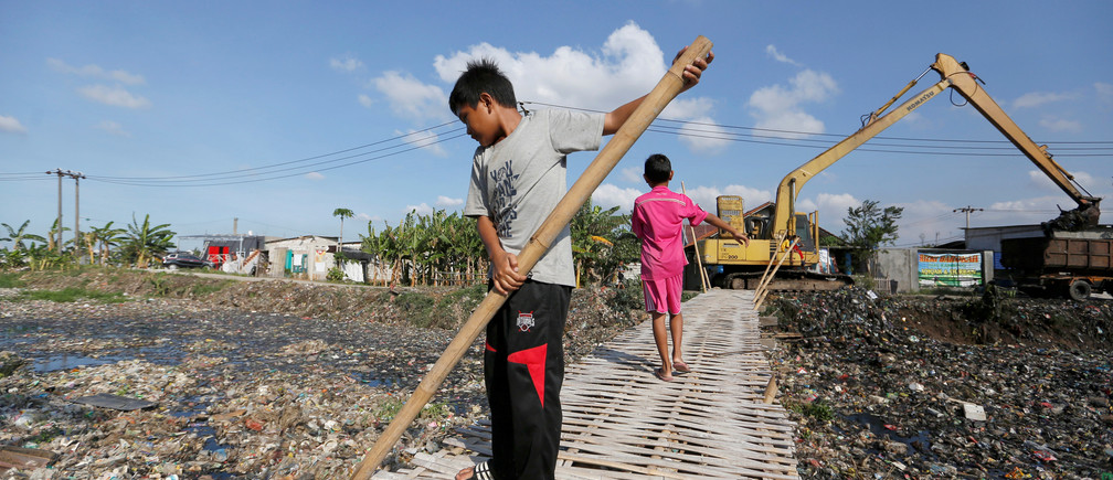 A boy uses a bamboo stick to clean a river covered by rubbish in Bekasi, West Java province, Indonesia, January 7, 2019. REUTERS/Willy Kurniawan - RC1B93BC5940