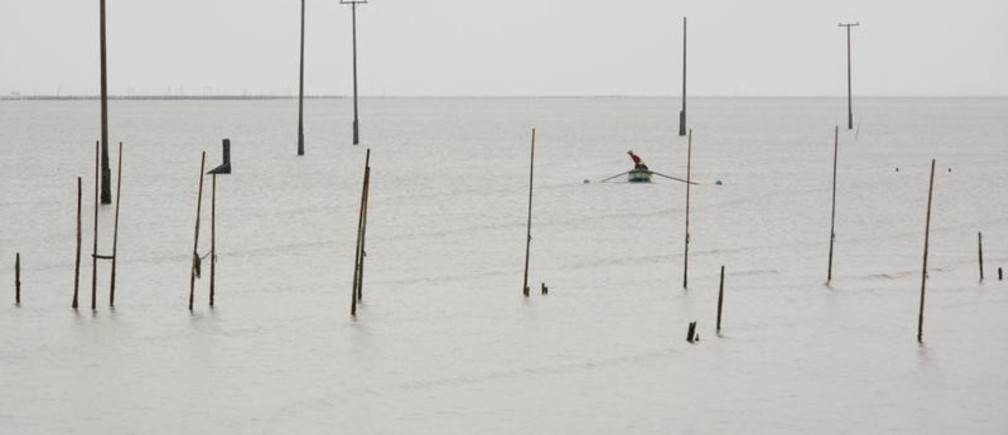 A man fishes near posts which once held power lines in the ancient coastal village Khun Samutjeen in Thailand's Samut Prakan province. Villagers in the area have been forced to relocated their homes due to rising sea levels and coastal erosion caused by climate change