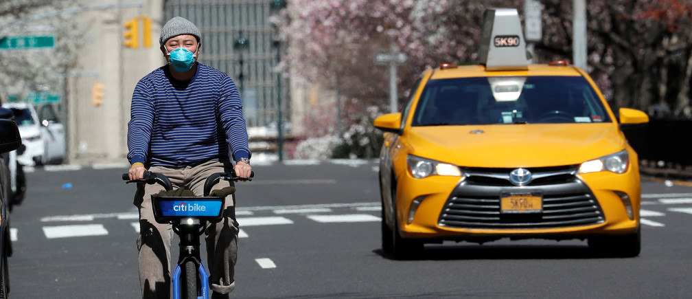 A man wearing a protective mask rides a bicycle on Park Avenue in midtown Manhattan during the outbreak of the coronavirus disease (COVID-19) in New York City, New York, U.S., March 24, 2020. REUTERS/Mike Segar - RC2IQF9LJ6YW