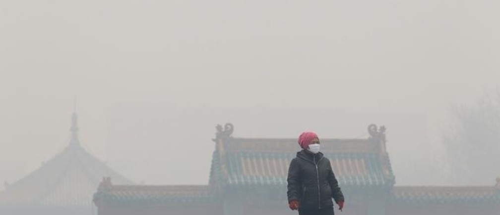 A woman wearing a mask walks outside the old palace museum on a hazy day in Shenyang, Liaoning province, November 8, 2015. As winter heating started in the city, the reading of PM2.5 was more than 1000 micrograms per cubic metre on Sunday, according to local media. Picture taken November 8, 2015. REUTERS/Stringer CHINA OUT. NO COMMERCIAL OR EDITORIAL SALES IN CHINA