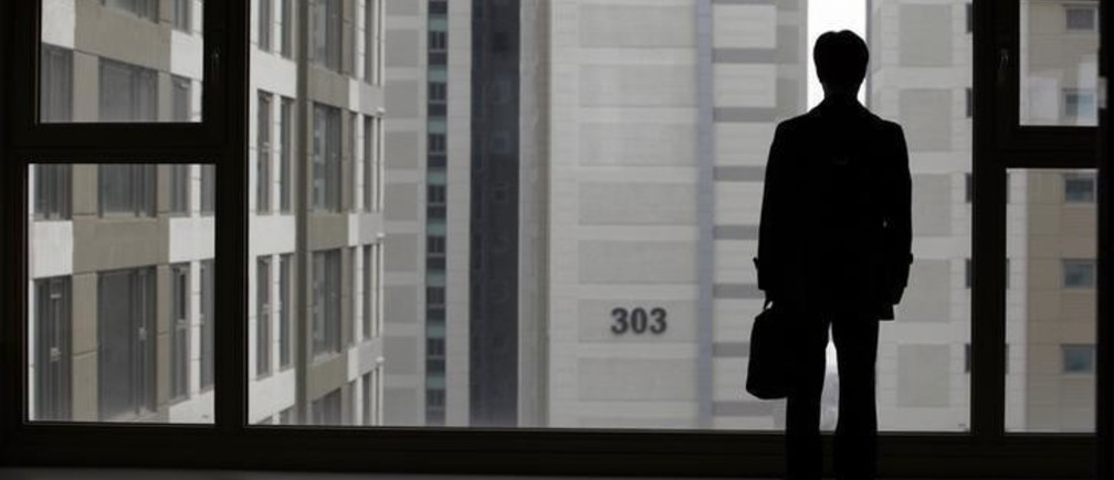 Kim Keon-hoon, a worker with Byucksan Engineering & Construction, looks out through the window from his empty two-bathroom, four-bedroom apartment before an interview with Reuters, in the middle class suburb in Goyang, north of Seoul April 1, 2013. Kim says he was forced to buy an unsold 800 million won ($716,400) apartment, built by his employer in 2008, as the company teetered on the edge of bankruptcy. Five years after the global financial crisis, South Korean construction workers are feeling the pinch more than ever as they shoulder a mountain of debt from a real estate bust that has cast a long shadow on the country's growth prospects. Picture taken April 1, 2013.   REUTERS/Lee Jae-Won (SOUTH KOREA - T