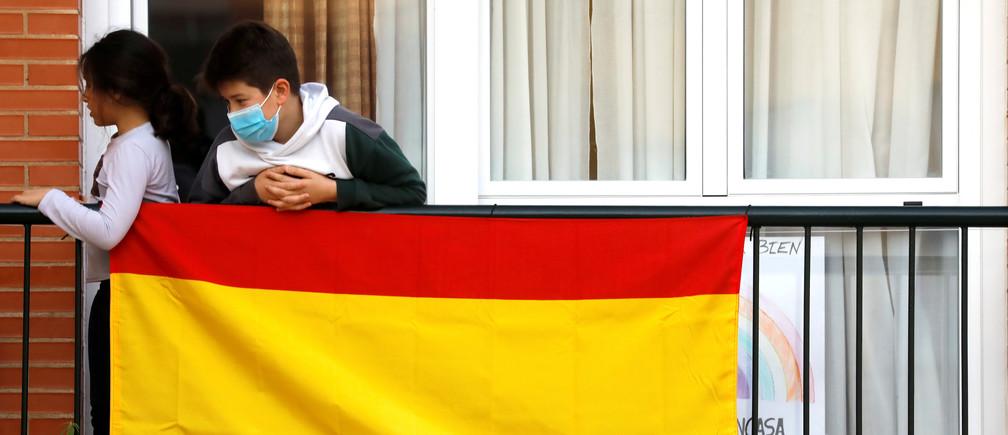 Un niño lleva una mascarilla protectora mientras su hermana juega a la pelota en el balcón de su casa, mientras esperan los aplausos diarios en apoyo de los trabajadores sanitarios durante el encierro, en medio del brote de la enfermedad coronavirus (COVID-19) en Ronda, al sur de España, el 22 de abril de 2020.