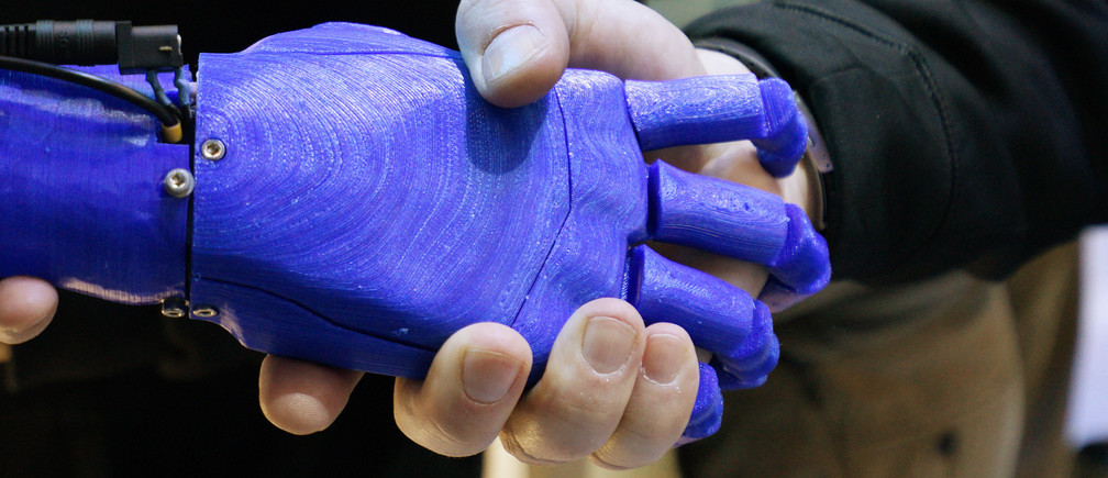 A man shakes hands with a robotic prosthetic hand in the Intel booth at the International Consumer Electronics show (CES) in Las Vegas, Nevada January 6, 2015.   REUTERS/Rick Wilking (UNITED STATES - Tags: BUSINESS SCIENCE TECHNOLOGY) - GM1EB170HRH01