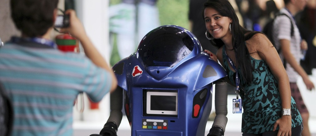 """A participant poses next to a robot during a """"Campus Party"""" Internet users gathering in Sao Paulo January 18, 2011."""