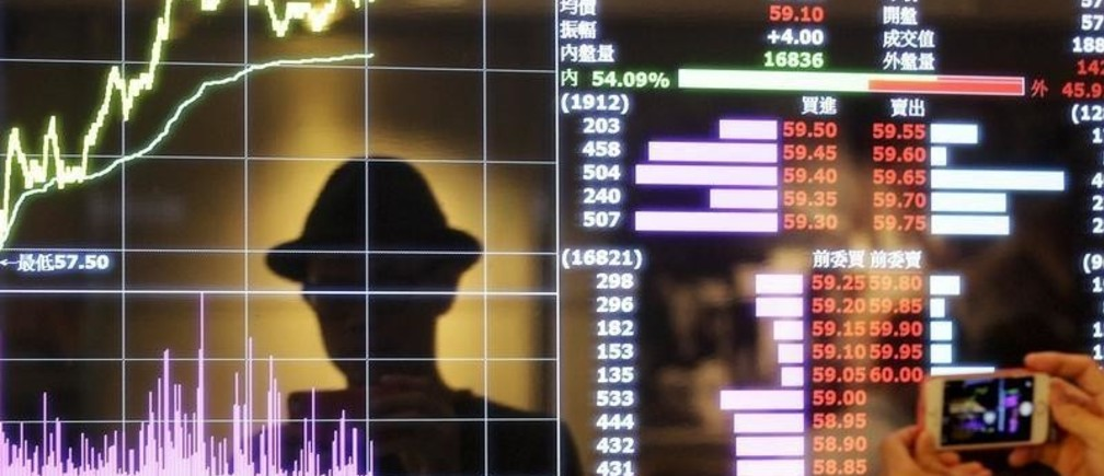 A man takes pictures with his smartphone at a screen showing stock market prices inside a brokerage in Taipei, Taiwan, August 25, 2015. Taiwan stocks rebounded from steep losses in the prior session on hopes the government would soon step in to shore up market confidence after the key index plunged to a near three-year low on Monday. REUTERS/Pichi Chuang      TPX IMAGES OF THE DAY      - RTX1PJIL