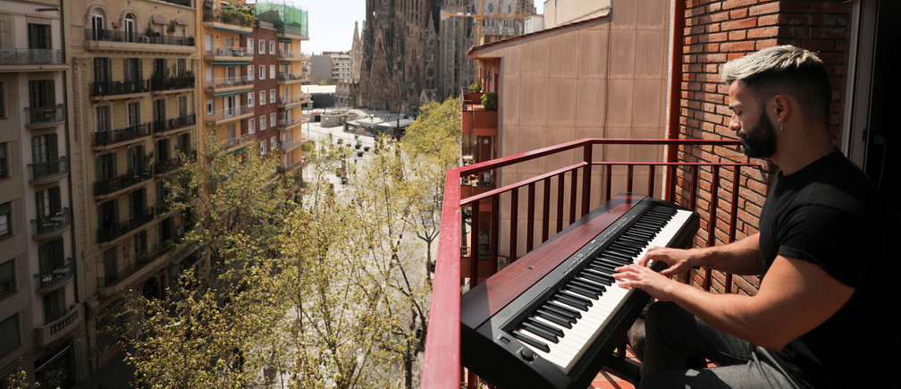 Amateur pianist Alberto Gestoso Arce, 37, plays the piano from his balcony for neighbours, near the Sagrada Familia basilica, during the coronavirus disease (COVID-19) outbreak in Barcelona, Spain March 21, 2020. Picture taken March 21, 2020. REUTERS/Nacho Doce - Coronavirus china virus health healthcare who world health organization disease deaths pandemic epidemic worries concerns Health virus contagious contagion viruses diseases disease lab laboratory doctor health dr nurse medical medicine drugs vaccines vaccinations inoculations technology testing test medicinal biotechnology biotech biology chemistry physics microscope research influenza flu cold common cold bug risk symptomes respiratory china iran italy europe asia america south america north washing hands wash hands coughs sneezes spread spreading precaution precautions health warning covid 19 cov SARS 2019ncov wuhan sarscow wuhanpneumonia  pneumonia outbreak patients unhealthy fatality mortality elderly old elder age serious death deathly deadly