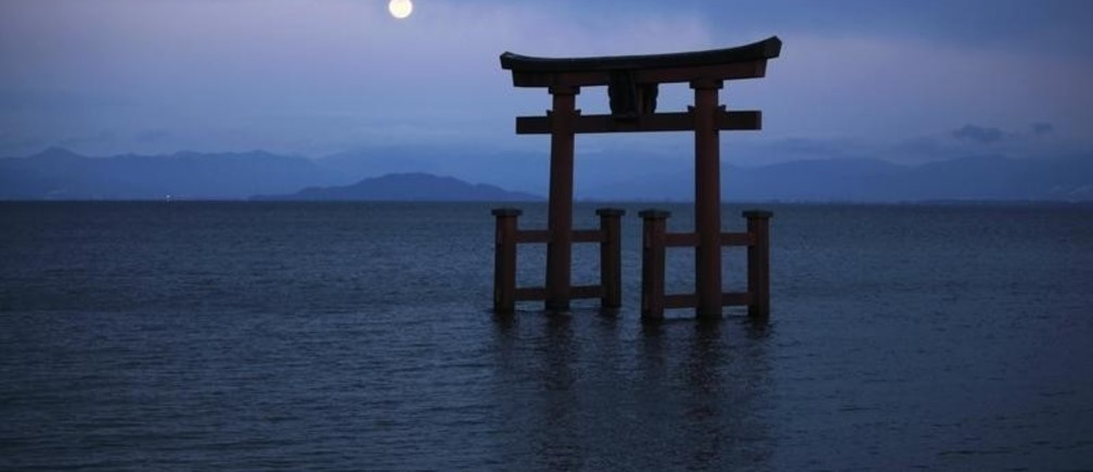 A Shinto shrine gate, with the moon behind it, is seen amidst Japan's largest lake, Lake Biwa, in Takashima, Shiga prefecture in western Japan April 6, 2012. Prefectures like Shiga, which have never been courted by the nuclear industry but lie close enough to reactors to be wary of them, are emerging as a serious complication for government and industry efforts to get nuclear power running again. Picture taken April 6, 2012. REUTERS/Toru Hanai