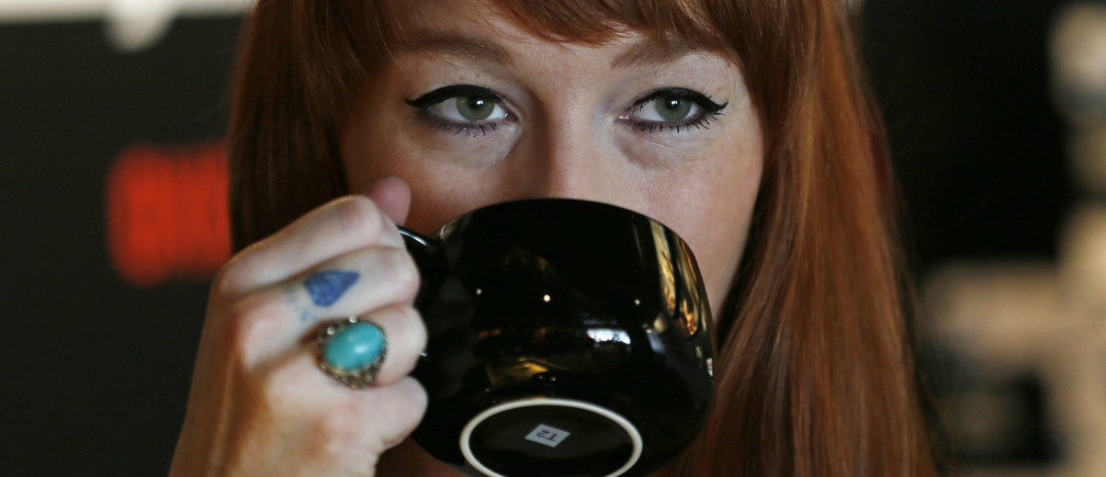 A woman drinks tea in a T2 shop in London April 24, 2014. Consumer goods giant Unilever is testing its might as a high-end retailer by opening the first European outpost of Australia's T2 tea chain on Thursday in London, hoping to reignite Britons' fading romance with the once-sacred cuppa. REUTERS/Stefan Wermuth (BRITAIN - Tags: BUSINESS FOOD SOCIETY) - LM1EA4O17L801
