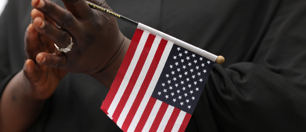 Fatoumata Jangana, from Gambia, claps holding an American flag during a naturalization ceremony at Franklin D. Roosevelt Four Freedoms Park, Roosevelt Island in New York City, U.S., June 16, 2017.  REUTERS/Shannon Stapleton - RTS17EP5