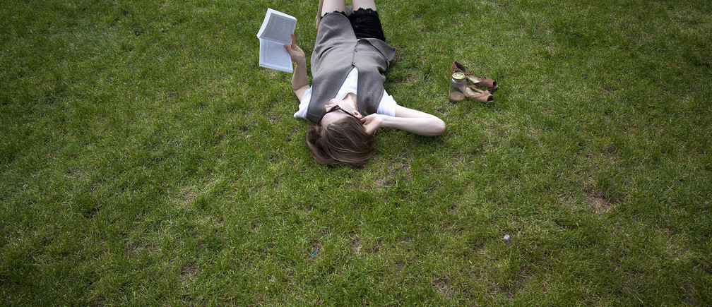 A woman lies in the grass while reading a book, at Columbia University in New York, April 14, 2014. The temperature reached an unseasonably high 77 Fahrenheit (25 Celsius). REUTERS/Carlo Allegri (UNITED STATES - Tags: SOCIETY ENVIRONMENT EDUCATION) - GM1EA4F0IVL01