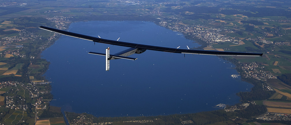 German test pilot Markus Scherdel steers the solar-powered Solar Impulse 2 aircraft over the Lake Murten during a training flight at its base in Payerne September 27, 2014. The aircraft, which was unveiled April 9, weighs 2.4 tons with a wingspan of 72 meters (236 ft.) and has more than 17,000 solar cells. The attempt to fly around the world in stages using only solar energy will be made from March 2015 starting from Abu Dhabi