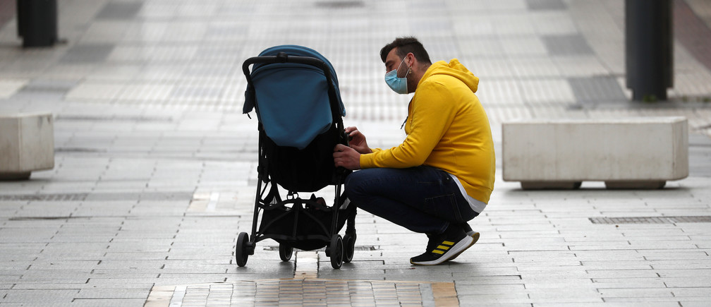 A man talks to his daughter sitting on a baby carriage in the empty La Bola street, after restrictions were partially lifted for children for the first time in six weeks, during the coronavirus disease (COVID-19) outbreak in Ronda, Spain, April 26, 2020. REUTERS/Jon Nazca - RC2ECG983NWG
