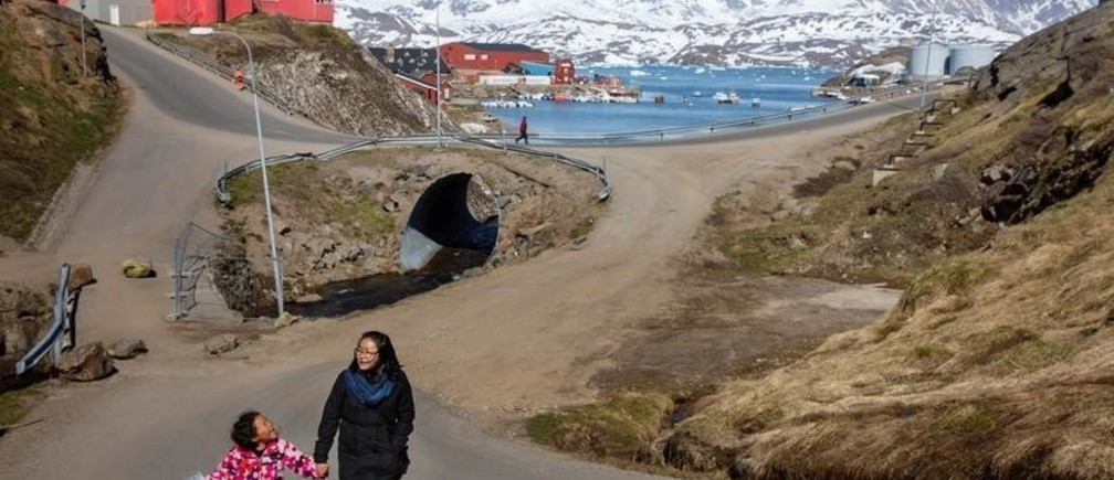 """A woman and child hold hands as they walk on the street in the town of Tasiilaq, Greenland, June 15, 2018. REUTERS/Lucas Jackson  SEARCH """"JACKSON TASIILAQ"""" FOR THIS STORY. SEARCH """"WIDER IMAGE"""" FOR ALL STORIES. - RC16202AB1F0"""