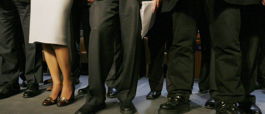 Shoes of Irish rock singer Bono (R) are seen as he stands next to Microsoft founder Bill Gates (C) and Jordan's Queen Rania to pose for photographers at the World Economic Forum (WEF) in Davos January 25, 2008.     REUTERS/Stefan Wermuth (SWITZERLAND) - RTR1W9MH