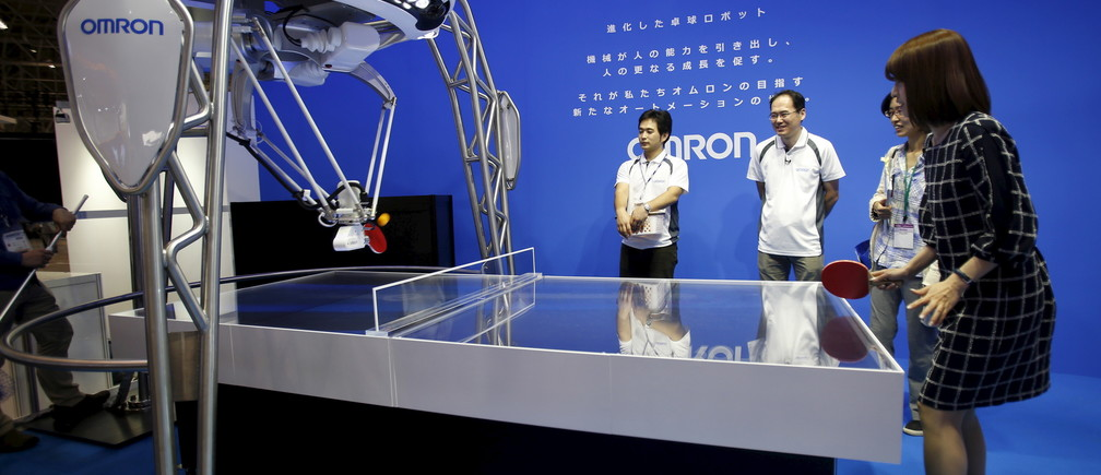 A woman plays table tennis with Japan's Omron Corp's table tennis playing robot at CEATEC (Combined Exhibition of Advanced Technologies) JAPAN 2015 in Makuhari, Japan, October 6, 2015. Over 500 companies and organisations are exhibiting at CEATEC JAPAN 2015, which will be held until October 10, 2015. REUTERS/Yuya Shino - RTS37EW