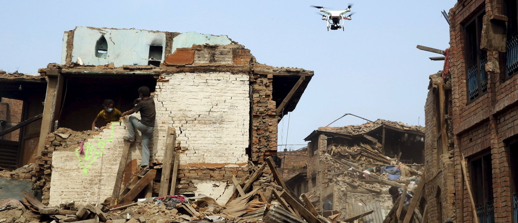 A drone flies over buildings destroyed after last week's earthquake in Bhaktapur, Nepal, May 2, 2015. REUTERS/Olivia Harris  - GF10000081001